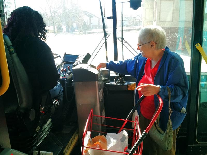 A resident of the Overland Park Towers Apartments pays 75 cents to ride to the grocery store.