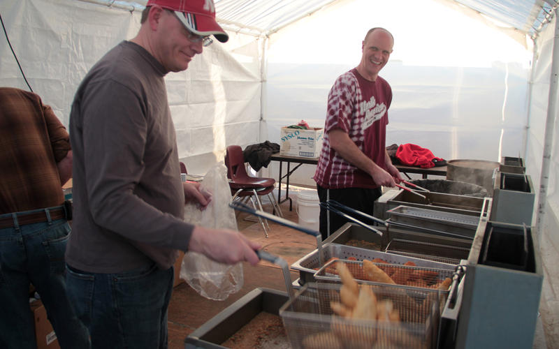 Gregg Hellbusch, left, drops a lod of fish into the fryer at the Friday night fish fry at North American Martyrs in Lincoln, Nebraska.