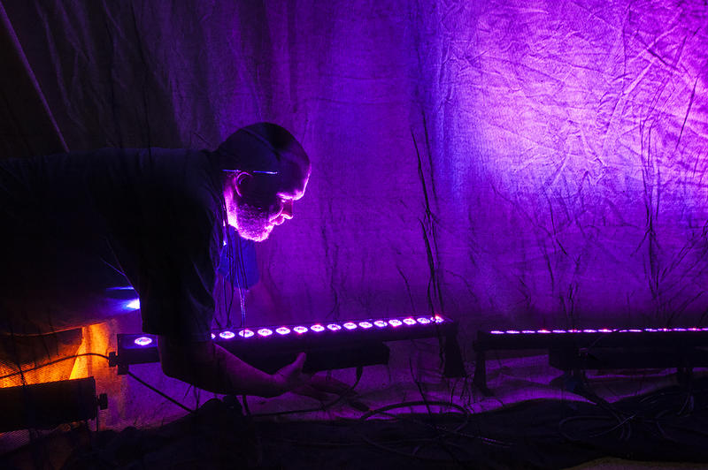 Stage Electrician Nick Uthoff works to position a set of LED lights behind a screen in preparation for 'The Ghosts of Lote Bravo' at Unicorn Theatre.