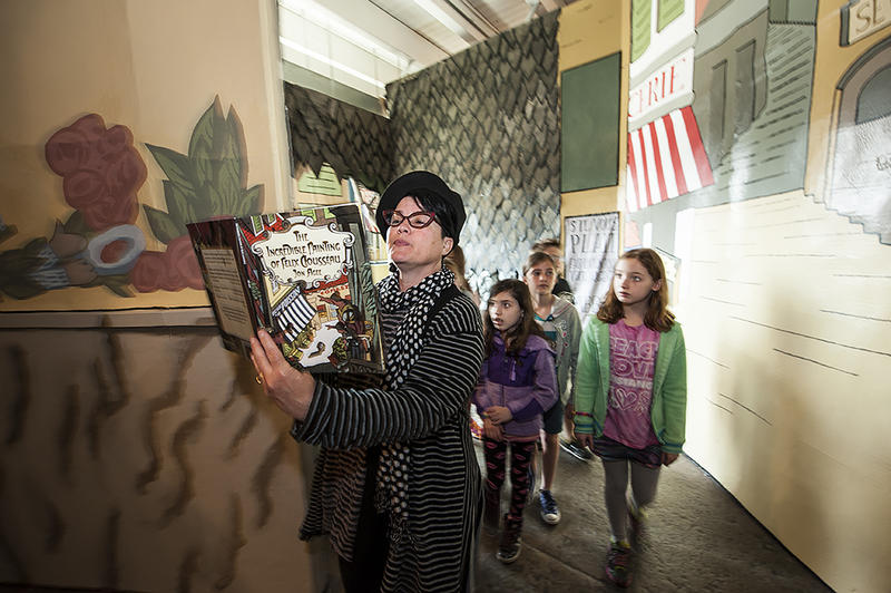 Docent Emily Sloan reads 'The Incredible Painting of Felix Clousseau' aloud as she leads a group of elementary school students into the exhibit space.