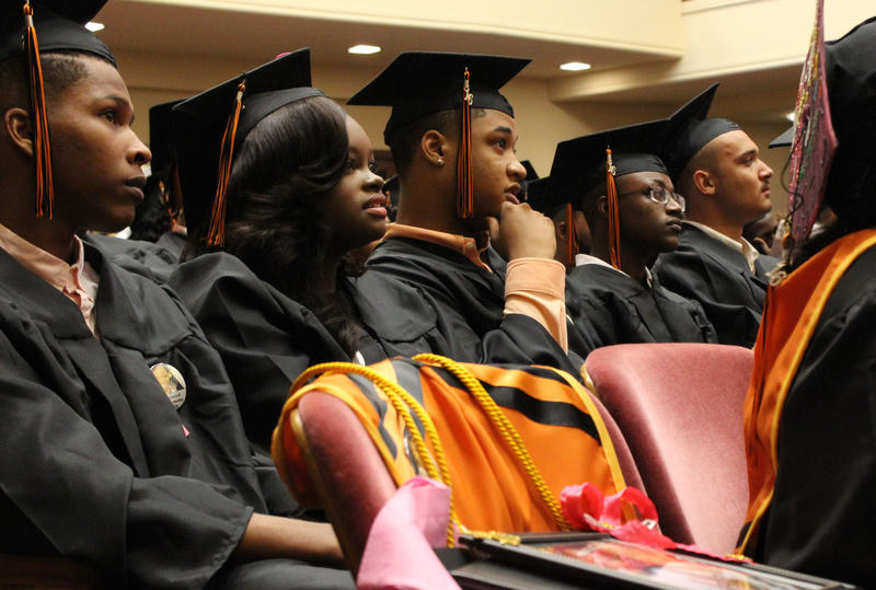 At the last graduation of Southwest Early College Campus, Nyla Brown listens to a performance by the Sunlight Baptist Church choir. In front of her, a seat remains open for classmate Daizsa Bausby, whose recent murder shocked, but pushed them to graduate.