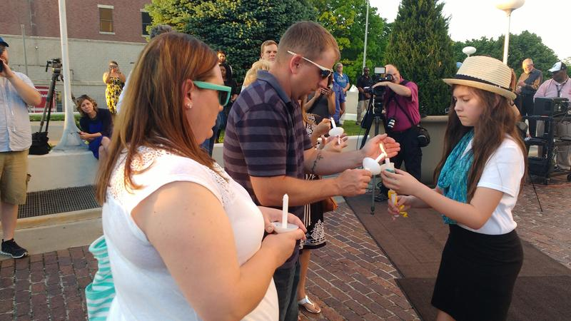 Detective Brad Lancaster's daughter Brianna circulated through the crowd lighting candles.