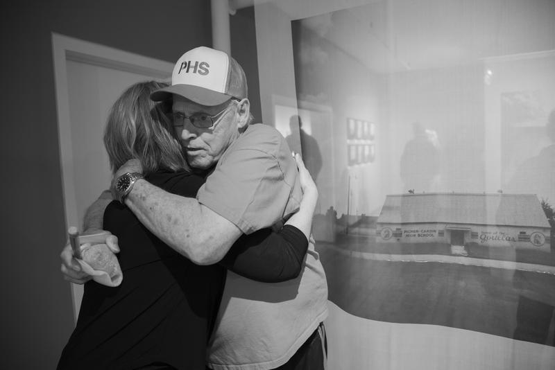 Former Picher, Oklahoma, resident Ray Moore embraces artist Sabrina Staires at the opening of her exhibition 'Echoes.'