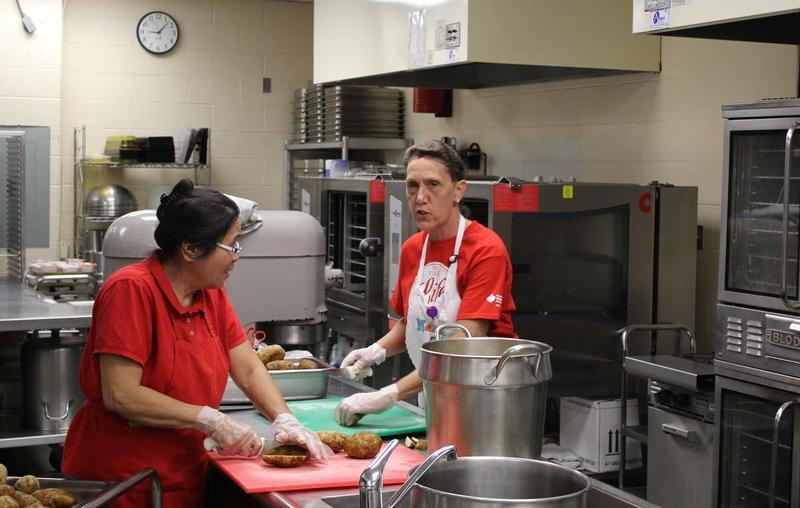 Lucia Wilson, left, and Rexie Schmuck chop potatoes in the kitchen at Eisenhower Middle School. Less than half of the schools in Topeka USD 501 operate their own kitchens.