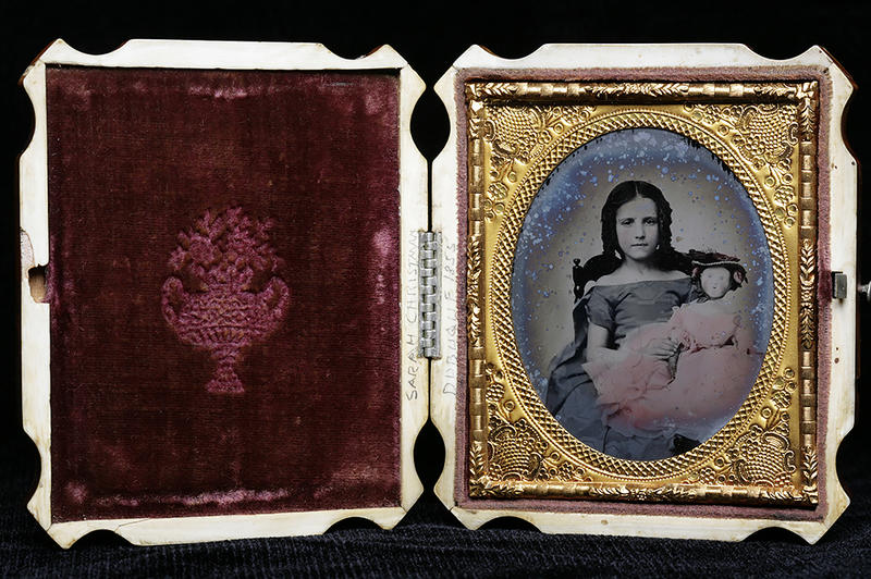 A hand-colored ambrotype of a girl with a doll in a pink dress. An ambrotype is a positive photograph on glass.