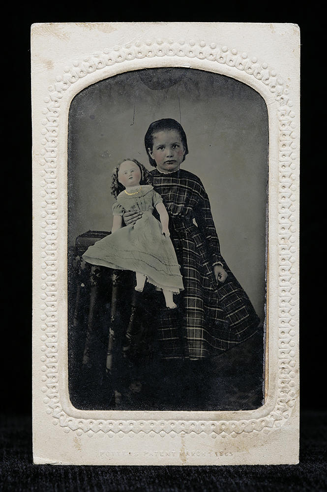A girl displays a doll in a hand-colored tintype.
