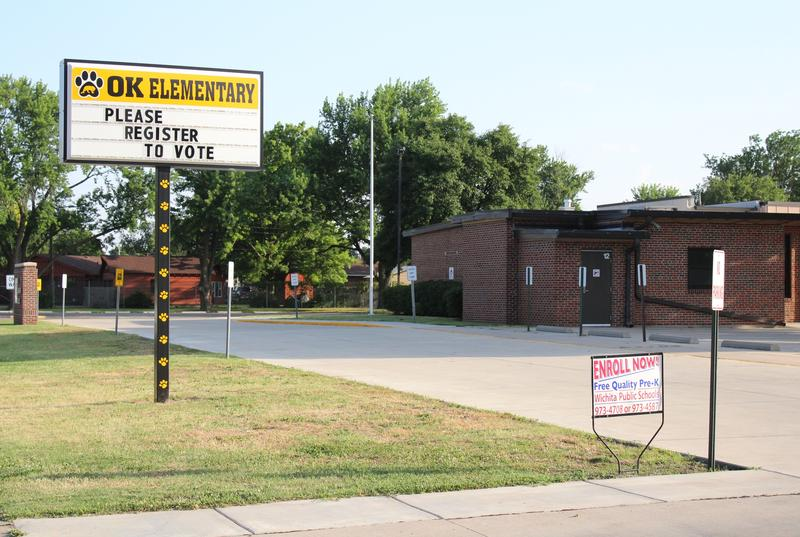 While many educators are spending the summer on the campaign trail, the sign outside a public elementary school in Wichita urges voters to register.