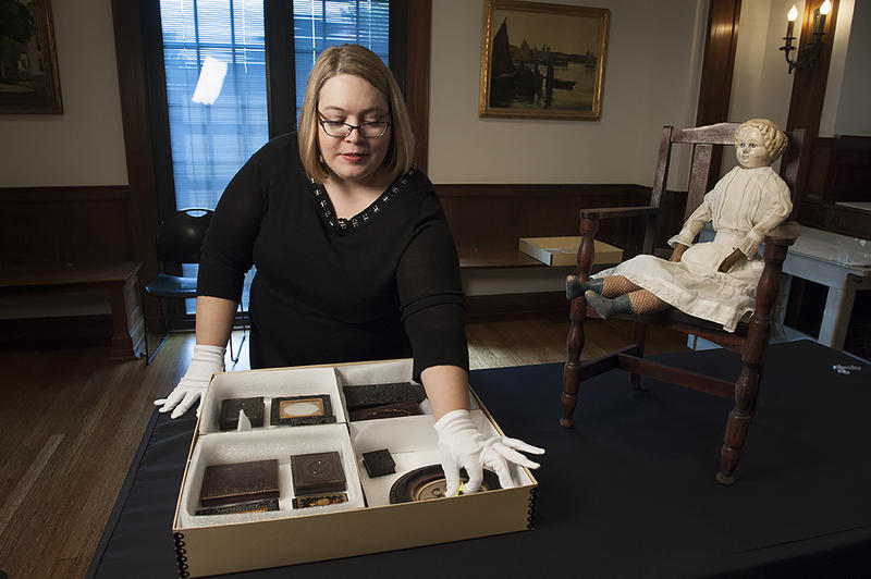 Dobbins arranges a box of Nick Vaccaro's private collection of photographs on loan to the museum.