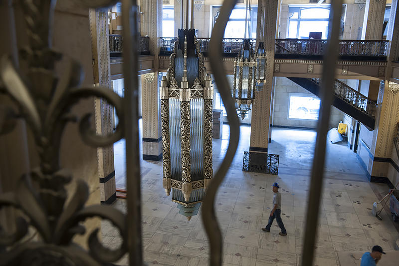 A worker walks beneath restored nickel-plated light fixtures at the Power & Lights Apartments.