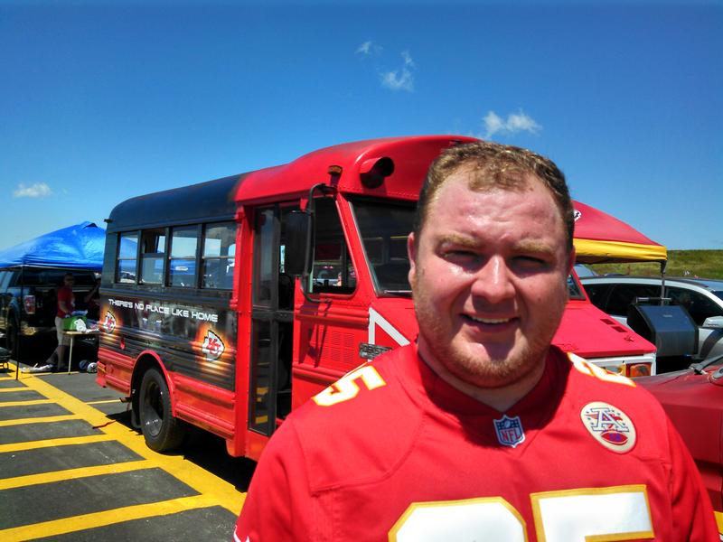 "Dallas Kidd stands in front of his ""There's No Place Like Home"" bus before a pre-season game at Arrowhead Stadium."