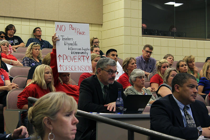 A teacher holds up a sign in protest at a recent Wichita School Board meeting where this year's contract was being discussed. Teachers were asking for raises and lighter workloads.