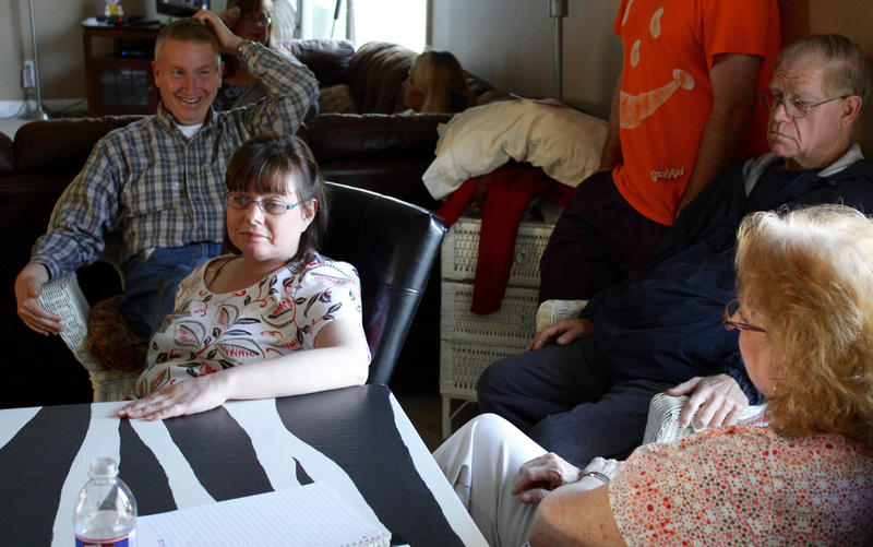 Cornerstone Supports clients Tom Newman, left, and Kim Vermillion, seated at table, talk with Kim's mom, Vickie, who owns Cornerstone. Vickie says she's closing the company because of state Medicaid reimbursement cuts.