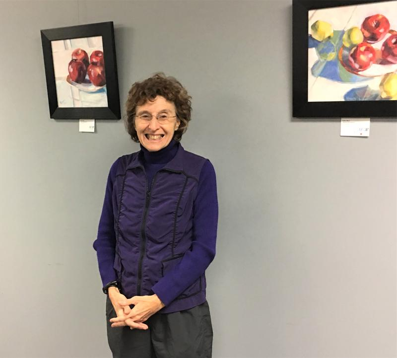 Kansas City writer Deborah Shouse says there are many ways for caregivers to connect to dementia patients through the expressive arts. She's standing next to paintings by artist Esther Boyd on view at KCUR.