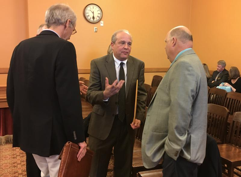 Rolfe Mandel, interim director of the Kansas Geological Survey, talks with Rep. Steven Crum, a Democrat from Haysville, after a legislative hearing Tuesday.  At left is James Butler of the geological survey.
