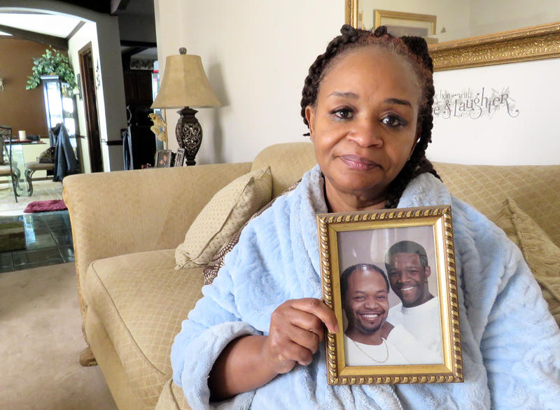Beverly Crawford holds a photo of her husband, Alvino, and their son Dwight. Dwight was murdered on July 5, 2016.