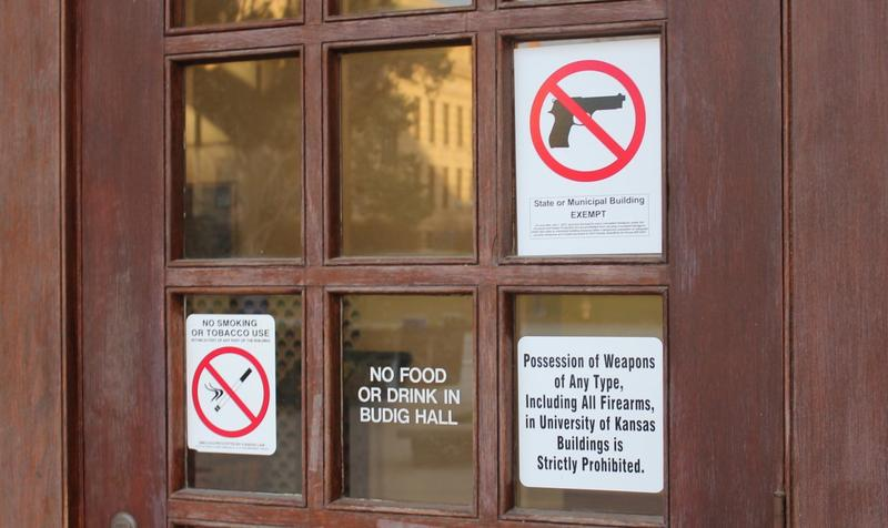 Signs barring guns hang on the door at Budig Hall on the University of Kansas campus.