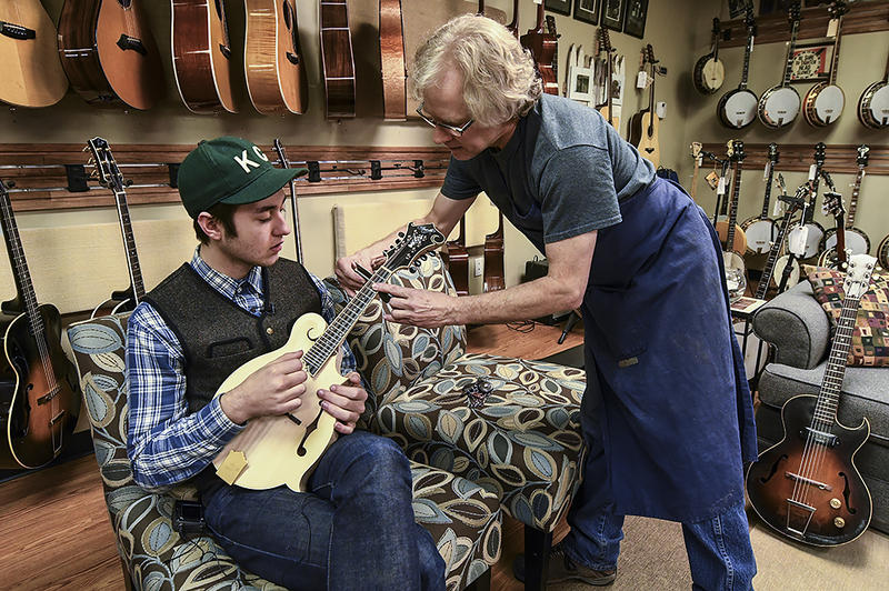 Musician Julian Davis holds an unfinished mandolin while luthier Mark Franzke measures the neck to fit Davis' hand.