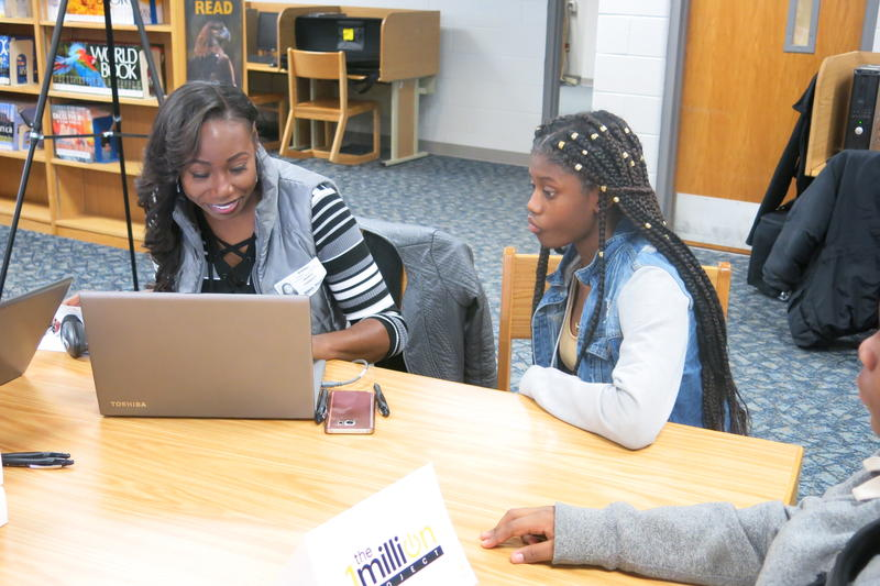 KCPS freshman Nia Abson, right, receives a wireless hotspot from a Sprint representative. Sprint is providing the wireless devices free of charge to low-income students who don't have internet access at home.