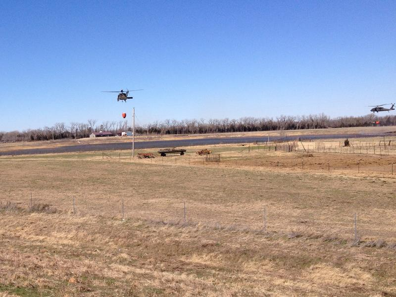 Blackhawk helicopters from the Kansas Army National Guard scoop water from a pond to fight wildfire north of Hutchinson.
