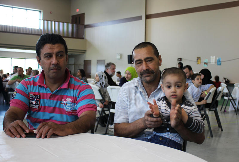 Mustafa Daghmoush, left, and Ahmad al-Abboud with his son Mohammed, right, are Syrian refugees who have resettled in Kansas City, Missouri in the last year. Al-Abboud and his wife are now expecting their sixth child.