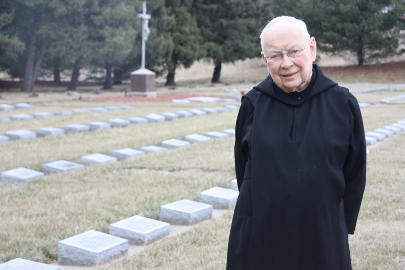 Father Dennis Meade in the abbey cemetery. The Benedictine Monks of Atchison established the monastery in Atchison, Kansas right around the time the state was opening for settlement.