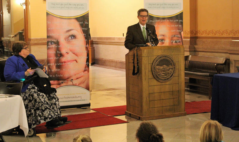 Kansas Department for Children and Families Secretary Phyllis Gilmore, left, listens as Gov. Sam Brownback speaks about the need for more foster parents during an event Wednesday at the Statehouse.