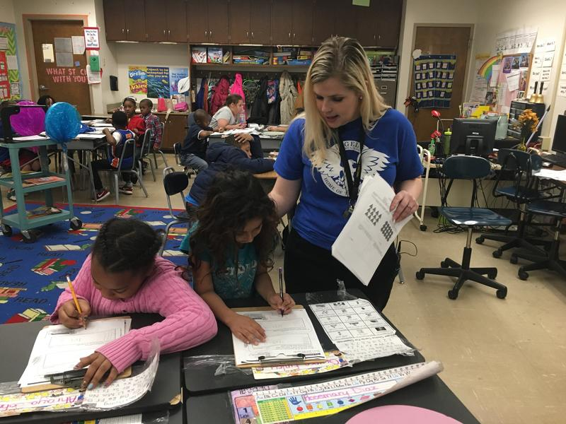 Second grade teacher Aubrey Paine helps students Ahraya and Rosemary with an assignment.