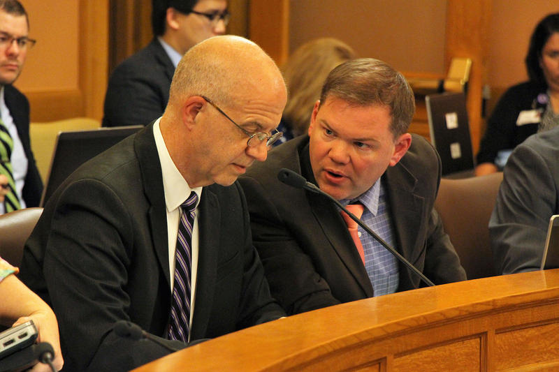 Kansas legislative research staff members J.G. Scott, left, and Dylan Dear confer while answering questions from lawmakers during Thursday night's negotiations. A panel of senators and representatives worked toward a compromise between two budget bills.