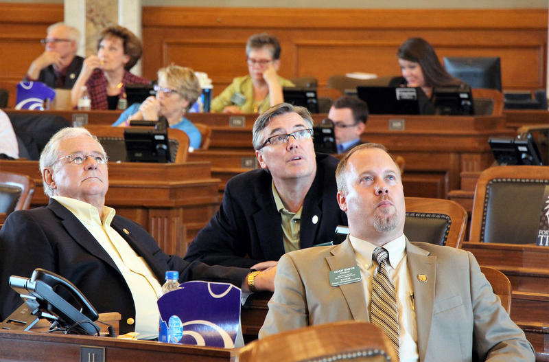Lawmakers in the House watch a vote board in suspense Saturday evening. The fate of the budget bill became unclear when some members voted against it or abstained. A procedural move forced the abstaining lawmakers to vote, and the bill passed.