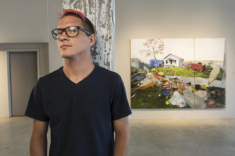 Travis Pratt with one of his paintings in the gallery space at Weinberger Fine Art. Pratt says he felt compelled to paint the scenes of devastation after family members lost their homes to Joplin's EF5 tornado.