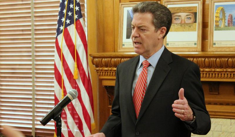 Gov. Sam Brownback signed the Kansas budget bill into law Sunday afternoon but used his line-item veto power to strike down portions that would block his administration from consolidating or modifying Medicaid services for Kansans with disabilities.