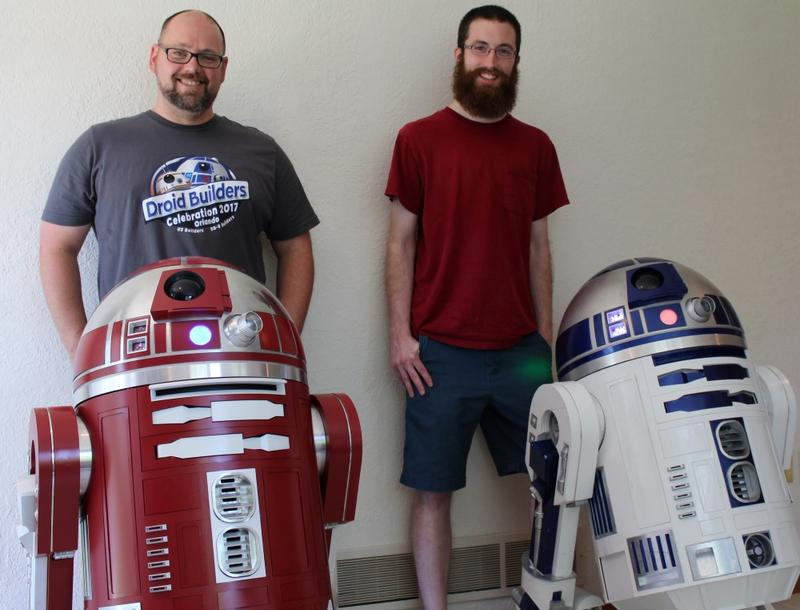 (left to right) Chris Leffel and Kevin Schwarz stand with the life-sized droids they've built: an R2-R9 and an R2-D2.