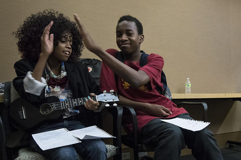 Teens Talaiha Johnson (left to right) and Sebastian Smith find a quiet corner to test out lyrics from different pop songs to the tune of 'Riptide' by Vance Joy. Teen Fringe's Open Mic Night gave them a chance to perform together for the first time.