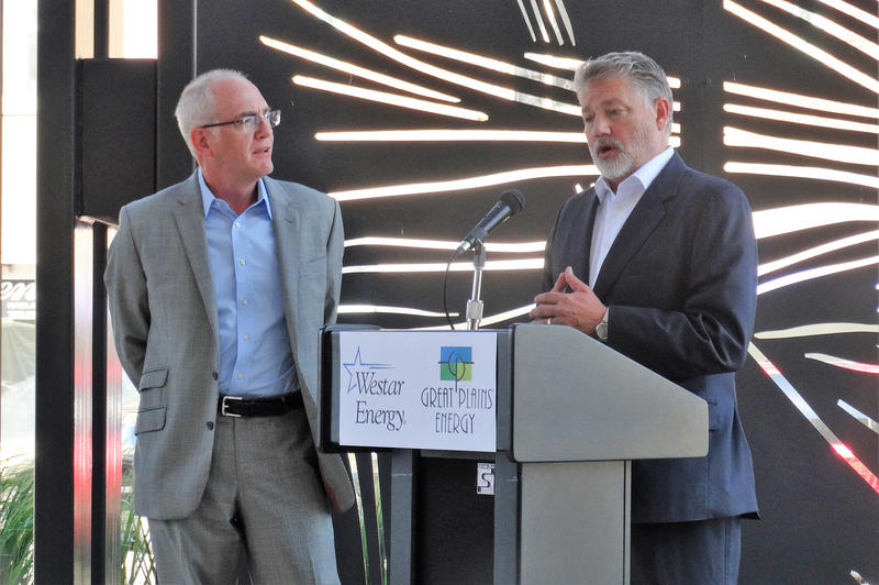 Mark Ruelle, left, president and CEO of Westar Energy, and Terry Bassham, president and CEO of Great Plains Energy, discuss a proposed merger of the two companies during a news conference Monday in Topeka.