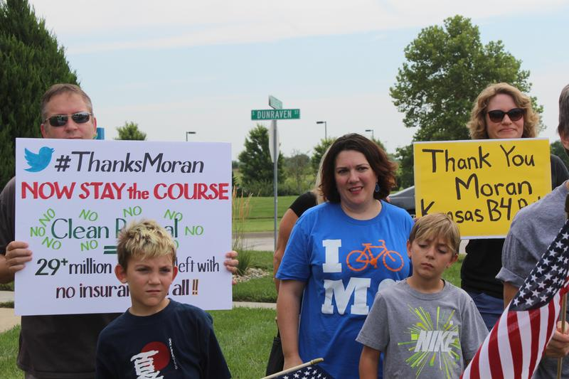 Demonstrators at the weekly protest outside Sen. Jerry Moran's Olathe office carried 'Thank You' signs Tuesday after the Senator stood firm against the Obamacare replacement bill. The mood shifted quickly with news Moran would still support repeal.