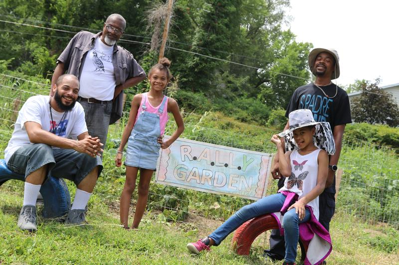 Richard Mabion, Terrell Dyer, his two daughter and Aaron Marks stand in front of the community garden they built on Alden St.