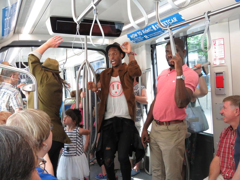 Street performer AY Young dances his way toward the center of the streetcar.