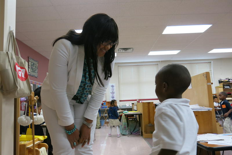 Principal KaLinda Bass-Barlow leans down to speak to a student. She is starting her second year at Holliday Montessori.