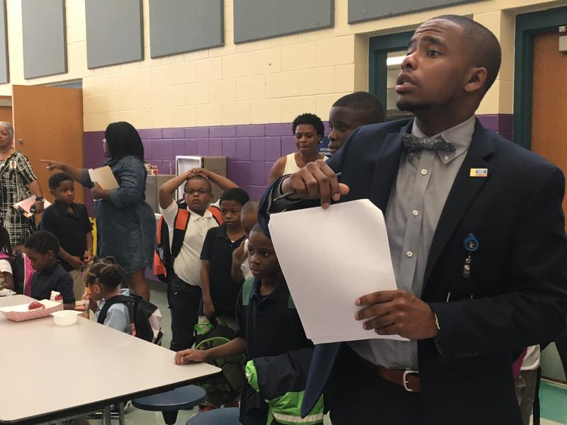 Principal Harrison Neal directs students eating breakfast to their classrooms at Banneker Elementary Monday morning.