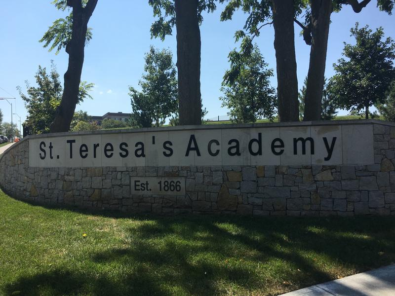 A group of St. Teresa's Academy students who posed next to beer pong cups in the shape of a swastika are allegedly harassing the student who reported them.