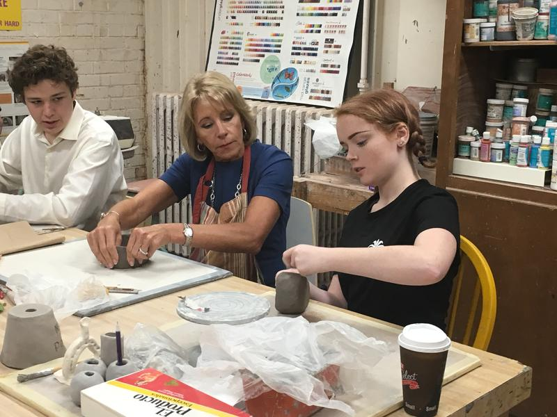 Kansas City Academy students Spencer Weis and Claire Harken teach U.S. Secretary of Education Betsy DeVos how to make a ceramic bowl.