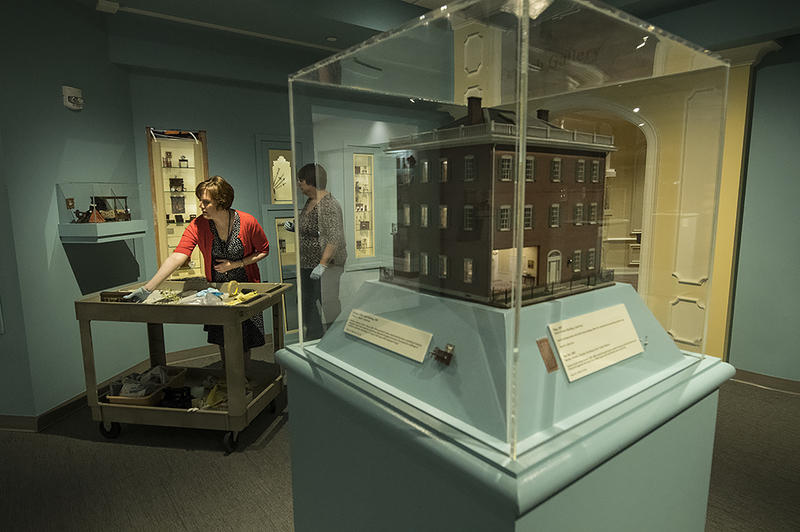 Laura Taylor (left), curator of interpretation at the National Museum of Toys and Miniatures, works with Amy McKune, curator of collections, to arrange a scene in a display case.