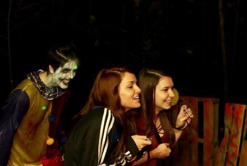 A creepy clown slinks behind two thrill seekers at Exiled, one of Kansas City's newest haunts.