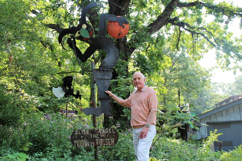At his Lake Quivira, Kansas home, Larry Meeker stands with M.T. Liggett's 'Clyde Angel The Moon Tosser.' Meeker is one of the four trustees charged with preserving Liggett's work.