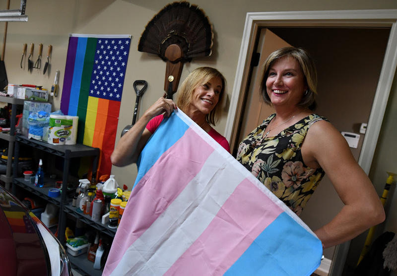 In the garage at their Shawnee home, Suzanne Wheeler and her fiancee, Marsha Riley, show off a transgender flag, with a gay pride flag on the wall.