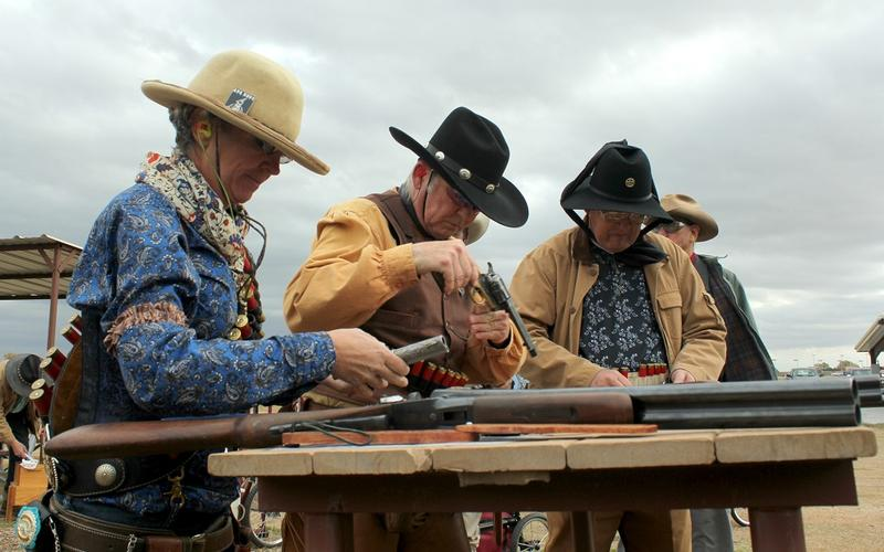 Members of the Single Action Shooting Society load their rifles and pistols at the Iron Hero match, including Danette Ray of Boulder, Colorado (left), aka Marie Laveau.