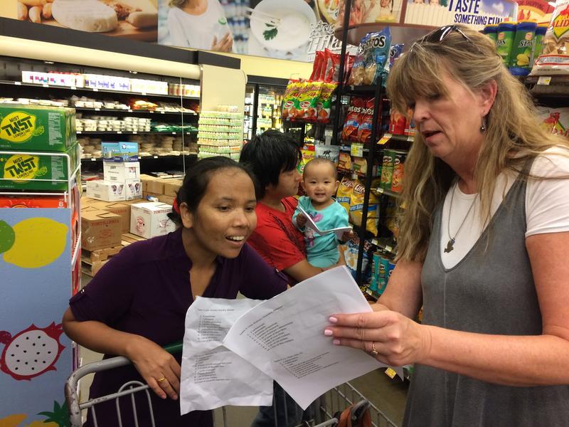 Debbie Buchholz helps Bhutanese refugee Harka navigate a grocery store.