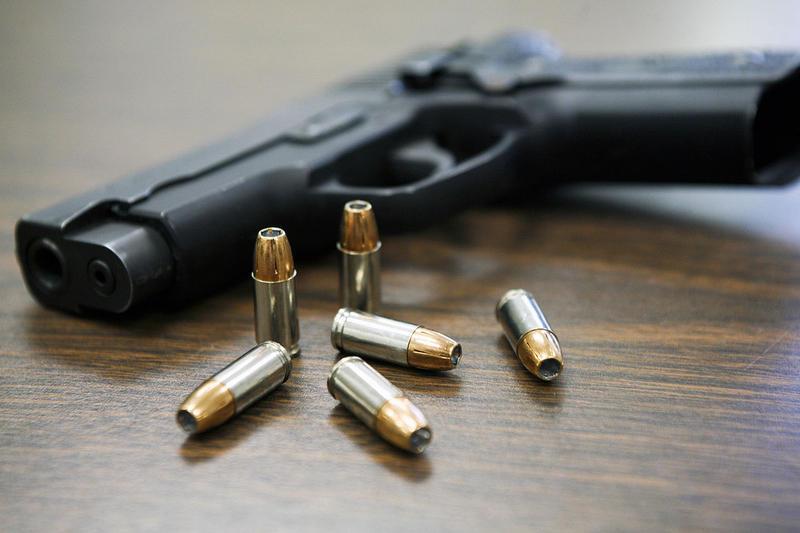 A handgun and six bullets on a desk.