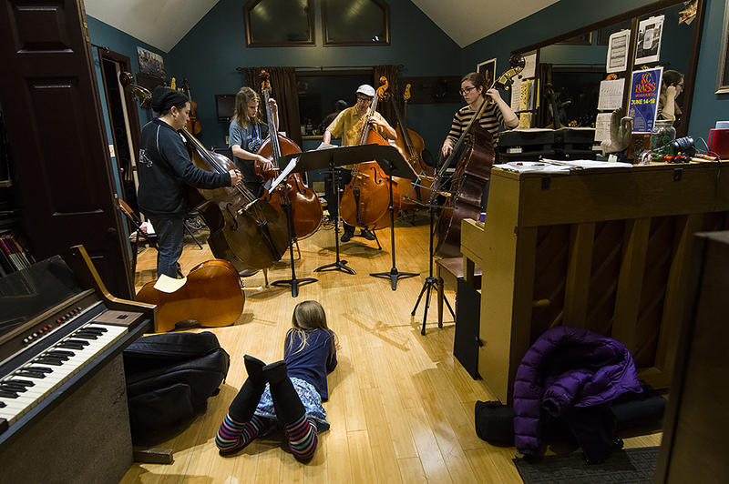 Professional bass player and teacher Johnny Hamil leads students through a rehearsal of holiday tunes at his home music studio in Mission, Kansas.