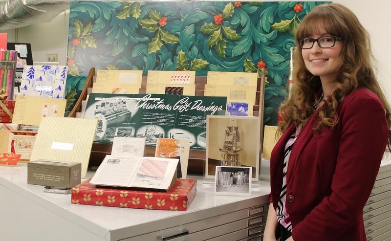 Hallmark Archives historian Samantha Bradbeer stands next to a display of early gift wrap samples.